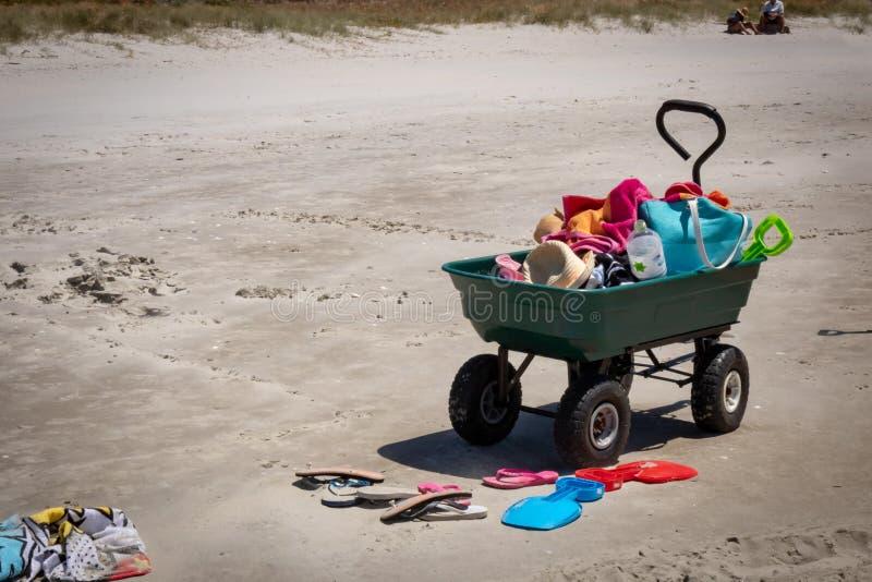 Plażowy zapluskwiony wheelbarrow, sandały i piasek rzeźby narzędzia, Matarangi plaża, Nowa Zelandia fotografia royalty free