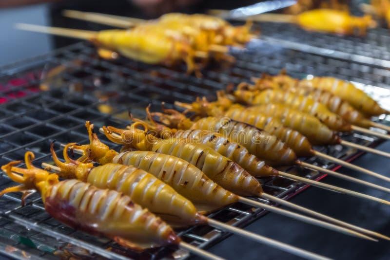 Pla Muek Yang - lo stile tailandese ha marinato arrostito sul calamaro del bastone immagini stock libere da diritti