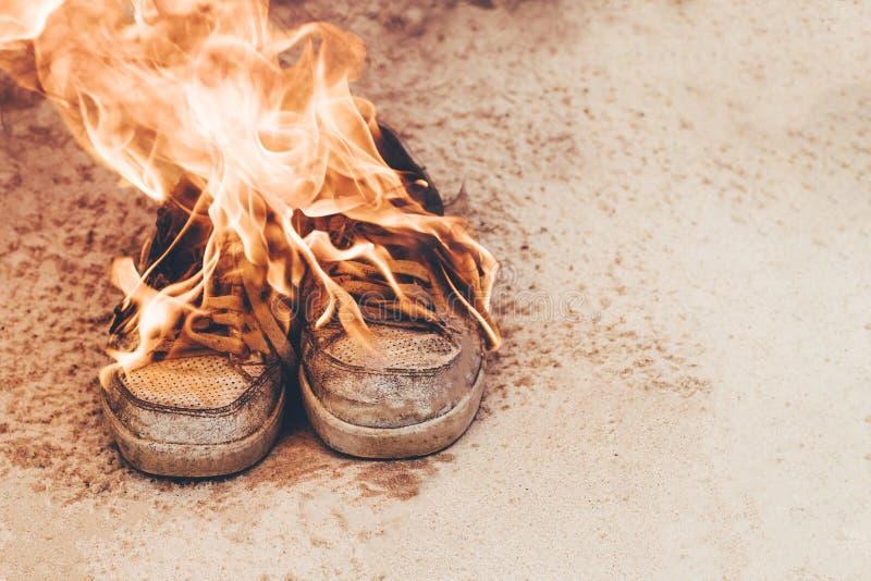 Pla?owy sand Sneakers są bardzo starzy pod otwierającym ogień, palenie pojęcia it& x27; s czas kupować nową parę buty obrazy stock