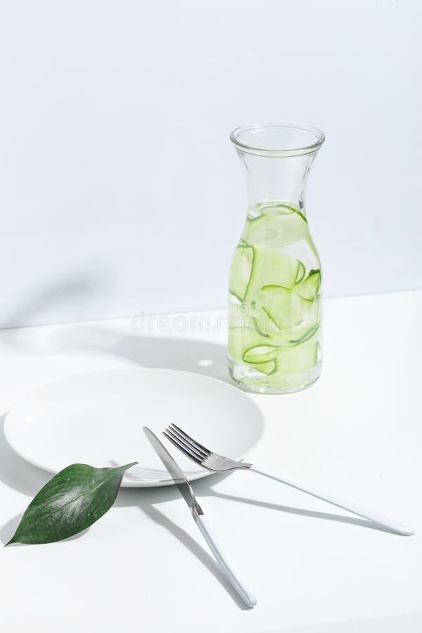 Plaat, bestek en kruik komkommerwater op een witte lijst Creatief minimalistic concept stock afbeelding