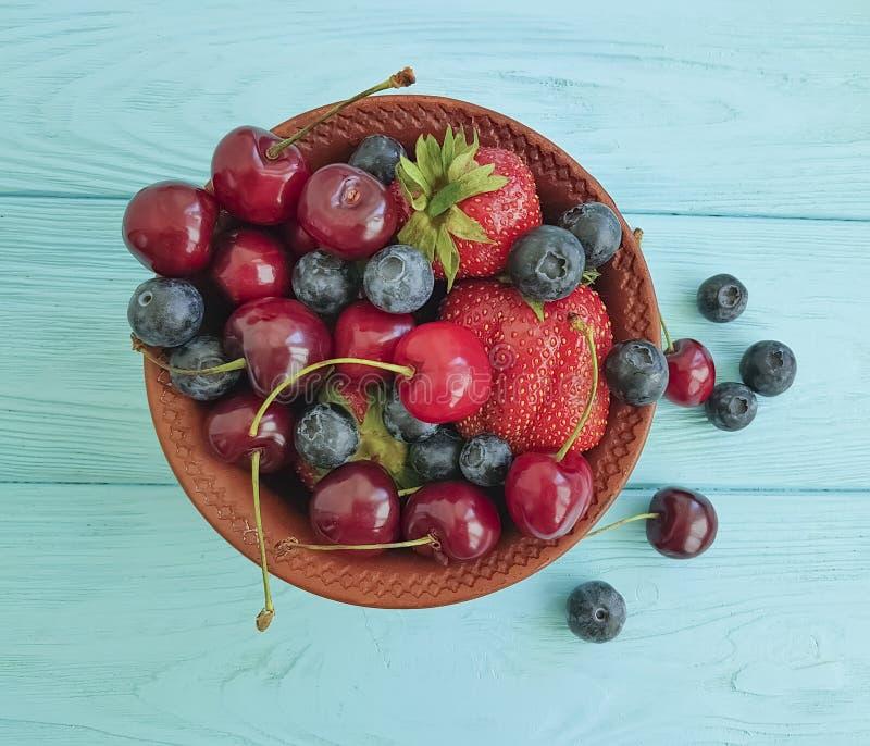 Plaat, fruitbessen, kers, aardbei, bosbessendessert op een blauwe houten achtergrond royalty-vrije stock afbeeldingen