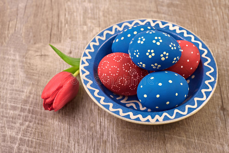 Plaat met blauwe en rode paaseieren en tulpenbloem op houten t royalty-vrije stock afbeelding