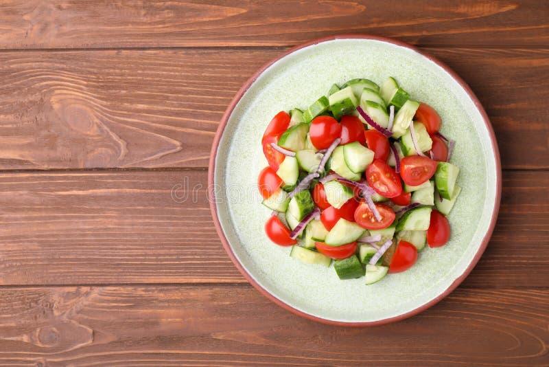Plaat met de heerlijke verse salade van de komkommertomaat op houten lijst, hoogste mening royalty-vrije stock afbeelding