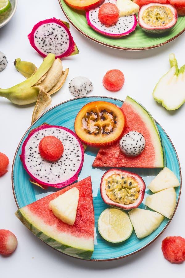 Plaat met de zomer diverse kleurrijke gesneden tropische vruchten en bessen op witte achtergrond, hoogste mening royalty-vrije stock fotografie