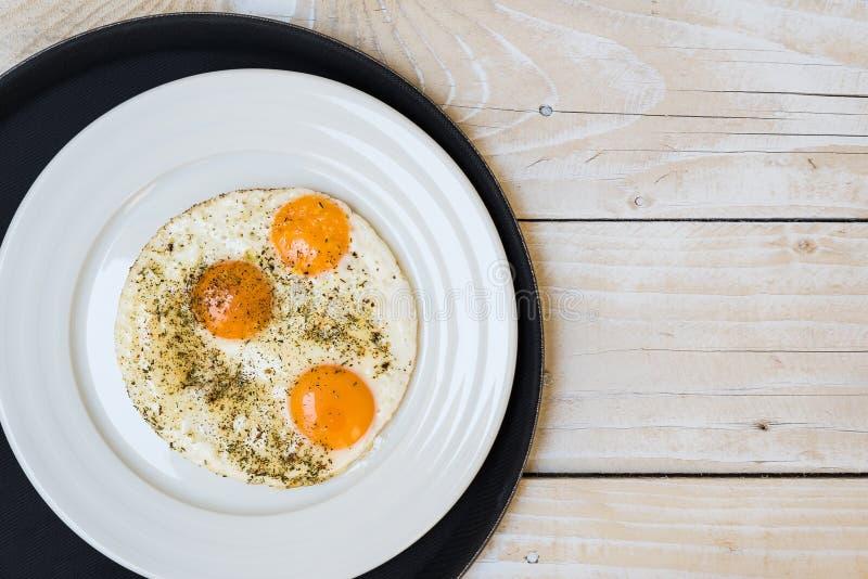 Plaat met gebraden eieren op zwart dienblad, houten lijst royalty-vrije stock foto