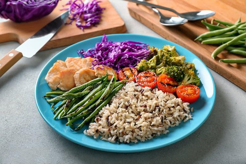 Plaat met gekookt rijst, groenten en vlees op grijze achtergrond stock fotografie