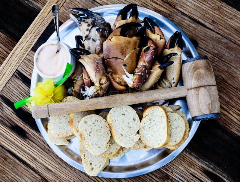 Plaat met gekookte benen en klauwen van bruine krab met brood en onderdompeling op houten lijst stock afbeeldingen