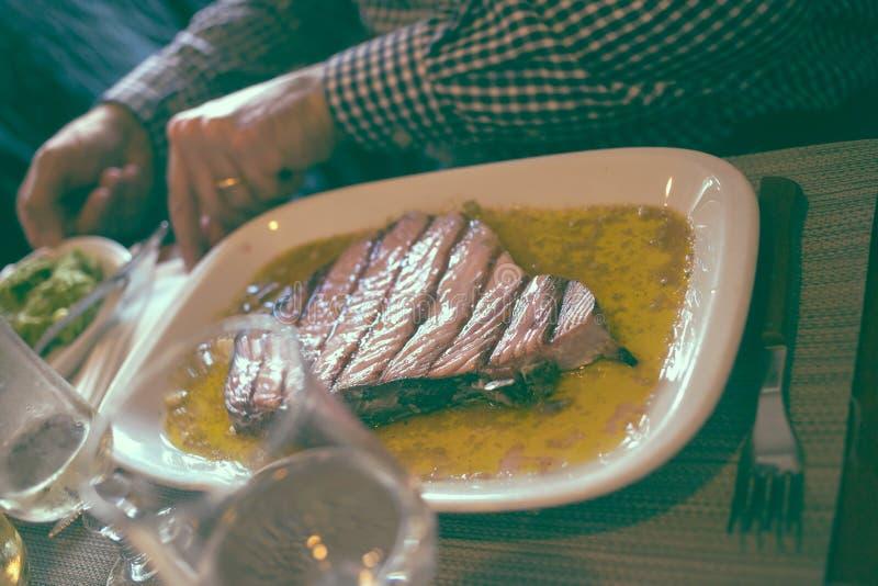 Plaat met geroosterde tonijn op lijst in restaurant stock foto