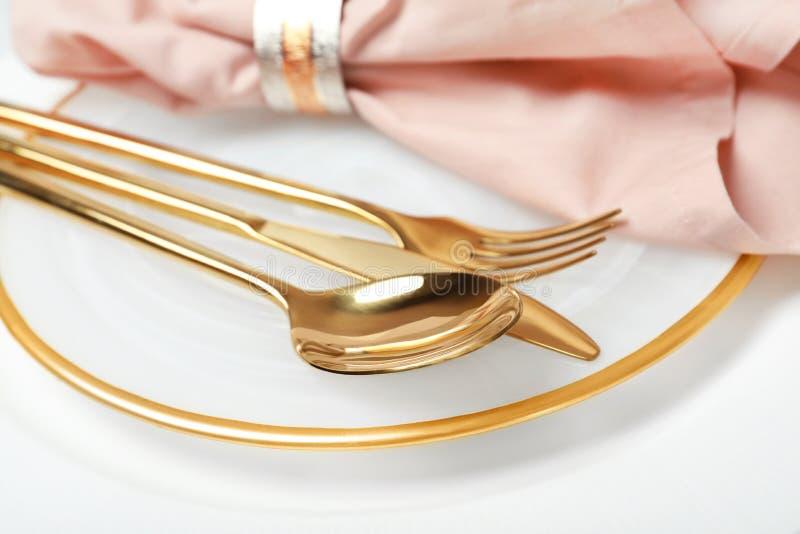 Plaat met gouden bestek en servet op lijst, close-up stock fotografie