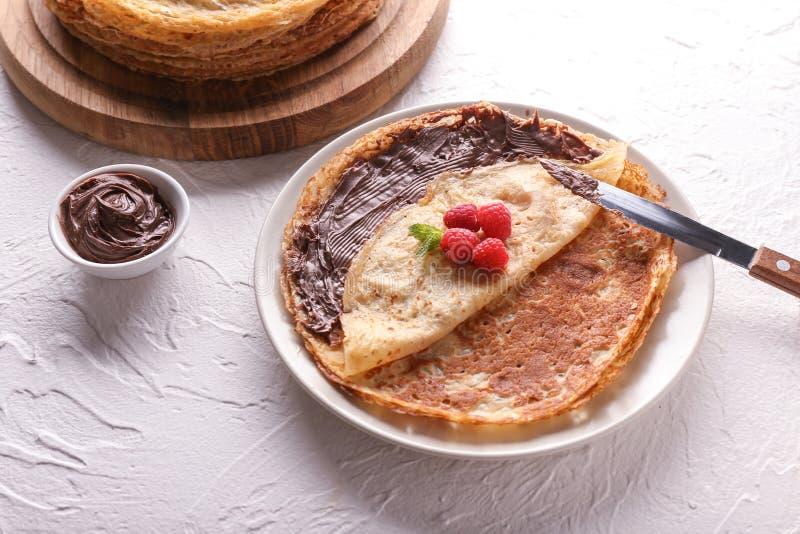 Plaat met heerlijke dunne pannekoeken, frambozen en chocoladedeeg op lichte lijst royalty-vrije stock afbeeldingen