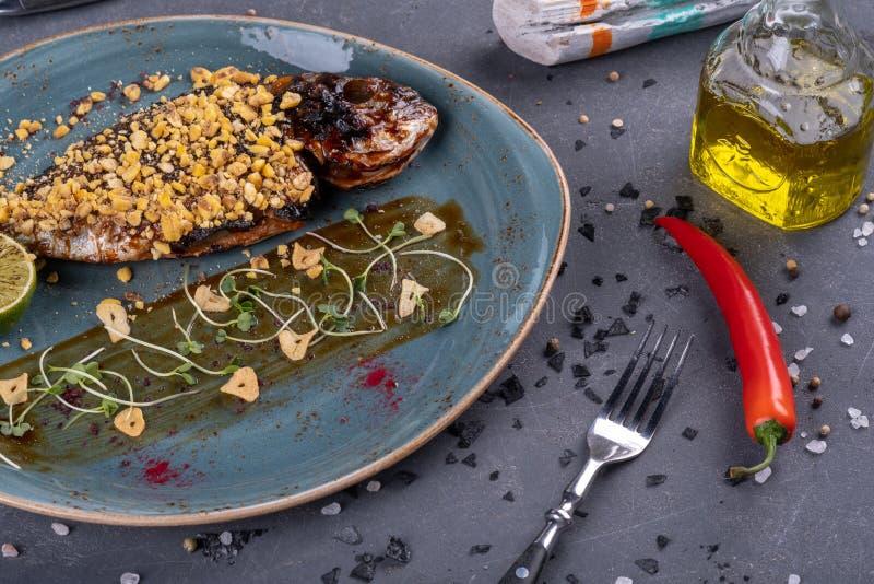 Plaat met heerlijke gebraden vissen op lijst Restautant het dienen op steenachtergrond stock afbeeldingen