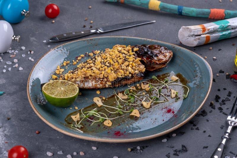 Plaat met heerlijke gebraden vissen op lijst Restautant het dienen op steenachtergrond royalty-vrije stock afbeelding