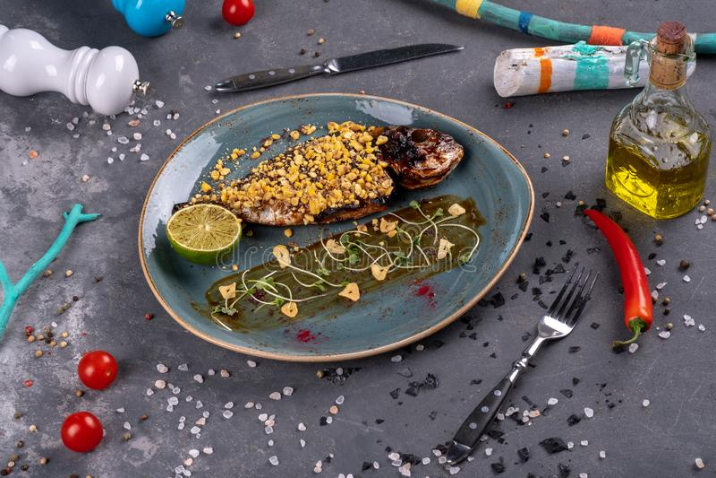 Plaat met heerlijke gebraden vissen op lijst Restautant het dienen op steenachtergrond stock afbeelding