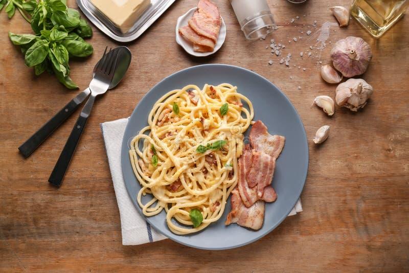 Plaat met heerlijke spaghetti en bacon op houten lijst, hoogste mening stock foto's
