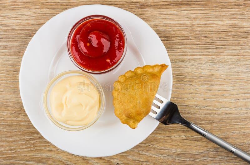 Plaat met ketchup en mayonaise en cheburek vastgebonden op vork stock fotografie