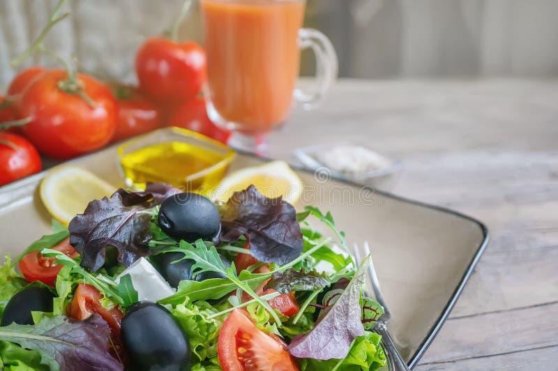 Plaat met keto dieetvoedsel Gehakte groenten voor het ketogenic dieet op een plaat Tomaten, salade met arugula, avocado en olijve stock afbeelding