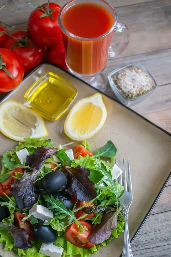Plaat met keto dieetvoedsel Gehakte groenten voor het ketogenic dieet op een plaat Tomaten, salade met arugula, avocado en olijve stock afbeeldingen