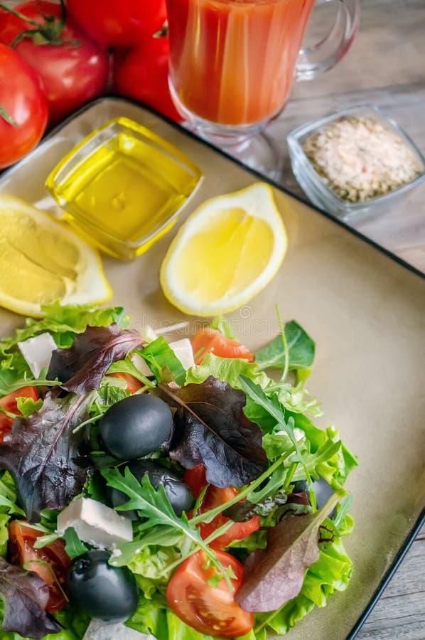 Plaat met keto dieetvoedsel Gehakte groenten voor het ketogenic dieet op een plaat Tomaten, salade met arugula, avocado en olijve royalty-vrije stock foto