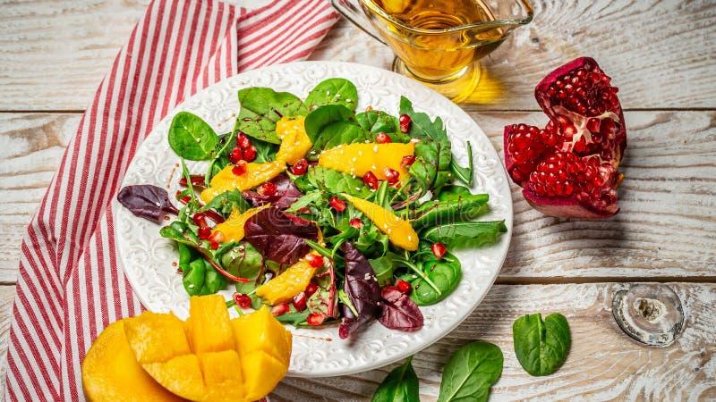 Plaat met lichte dieetsalade van arugula, mango en granaatappel Het schone eten, detox, vegetarisch voedselconcept stock foto