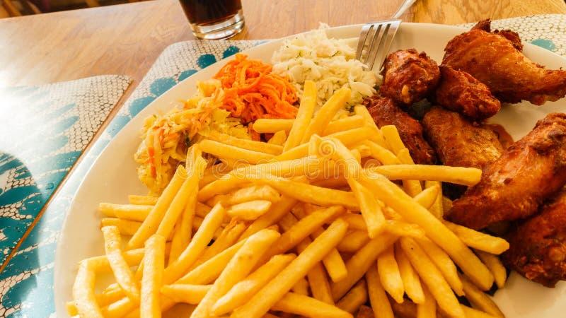 Plaat met maaltijd, spaanders, kippenvleugels en salade royalty-vrije stock foto
