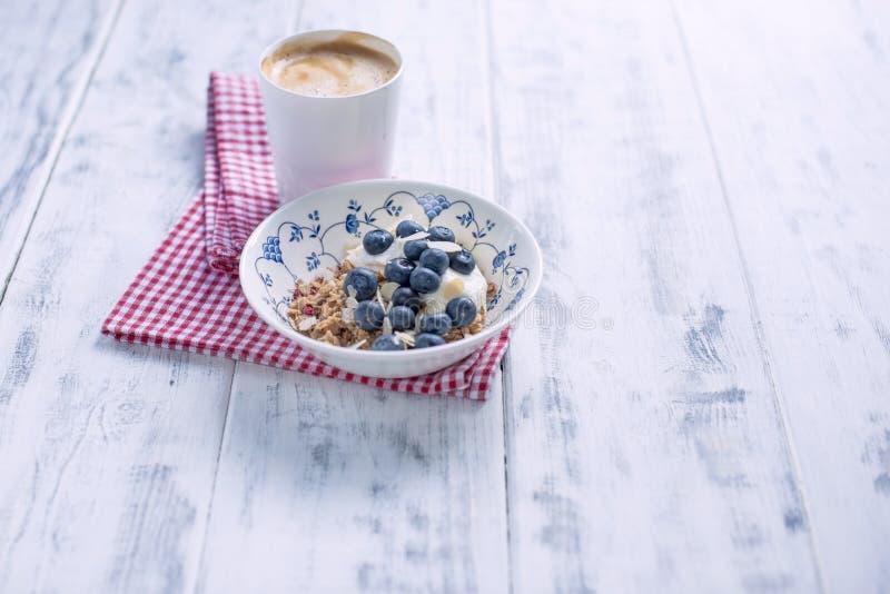Plaat met muesli en bessen, koffie in een kop voor ontbijtservet in een rode kooi op een witte houten lijst door het venster Vrij royalty-vrije stock afbeelding