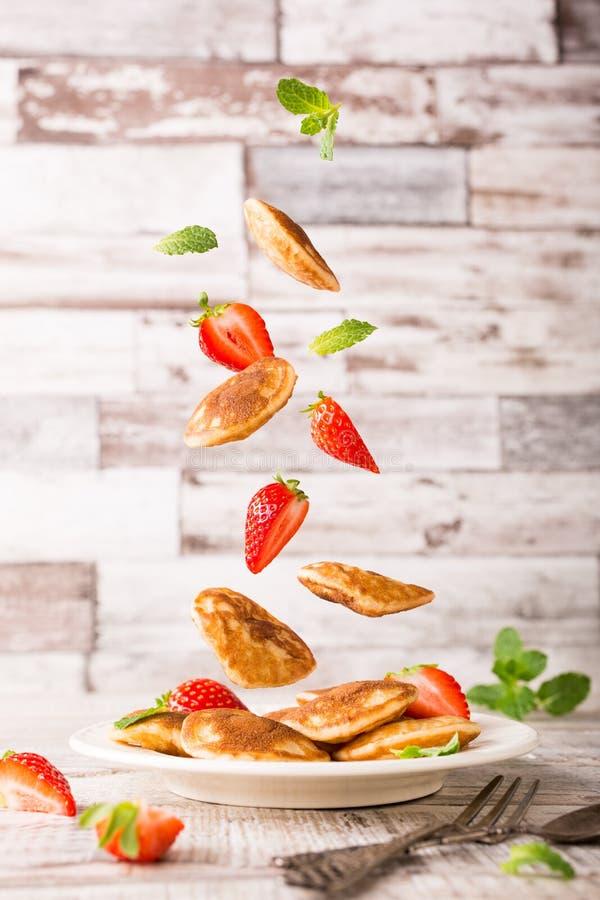Plaat met Nederlandse mini geroepen pannekoeken poffertjes en vliegende ingrediënten stock foto's