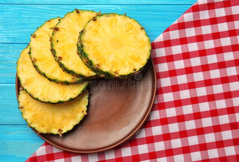 Plaat met plakken van rijpe ananas met servet op houten lijst royalty-vrije stock afbeeldingen