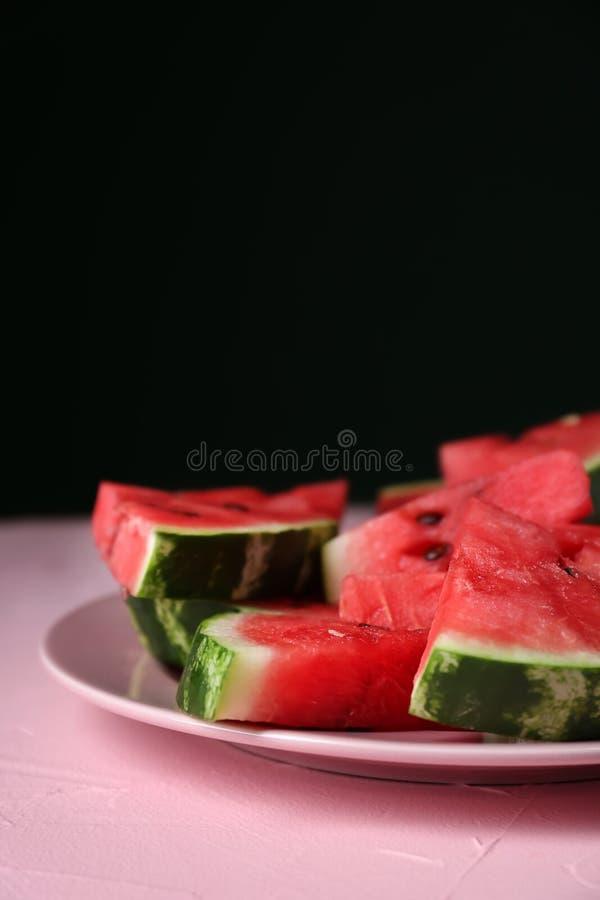 Plaat met plakken van rijpe watermeloen op kleurentabel tegen donkere achtergrond stock afbeelding