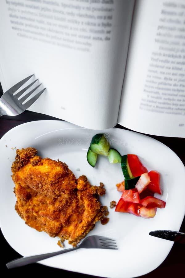 Plaat met schnitzel en salade en open boek royalty-vrije stock afbeeldingen