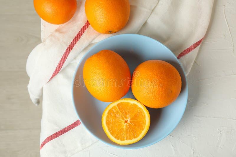 Plaat met sinaasappelen en keukenhanddoek op witte achtergrond royalty-vrije stock fotografie