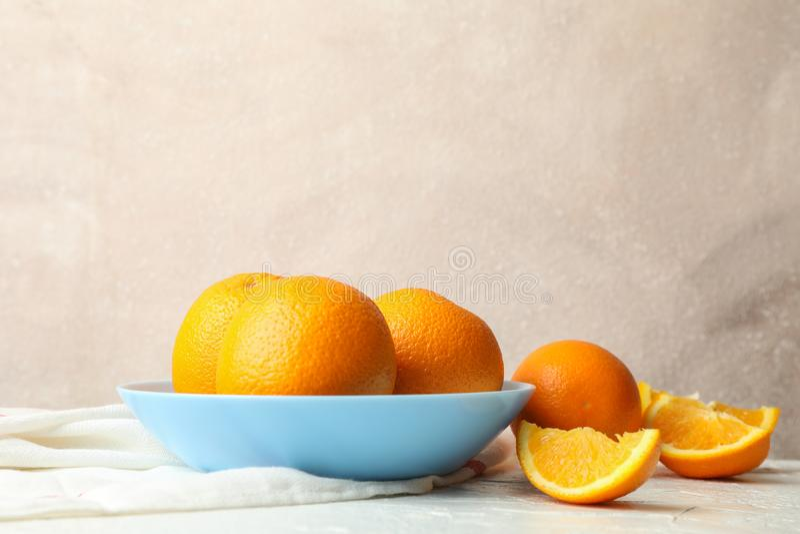 Plaat met sinaasappelen en keukenhanddoek op witte lijst tegen lichte achtergrond stock afbeeldingen