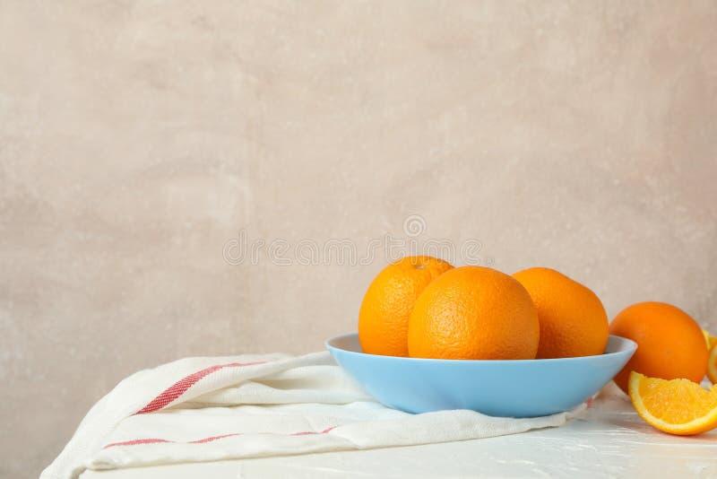 Plaat met sinaasappelen en keukenhanddoek op witte lijst tegen lichte achtergrond royalty-vrije stock fotografie