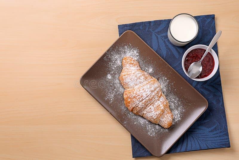 Plaat met smakelijk croissant, glas melk en jam stock afbeeldingen