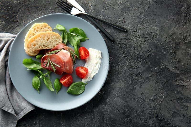 Plaat met smakelijk prosciutto, groenten en brood op lijst royalty-vrije stock fotografie
