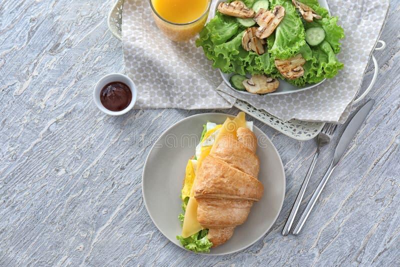 Plaat met smakelijke croissantsandwich en verse salade op lichte lijst royalty-vrije stock afbeelding