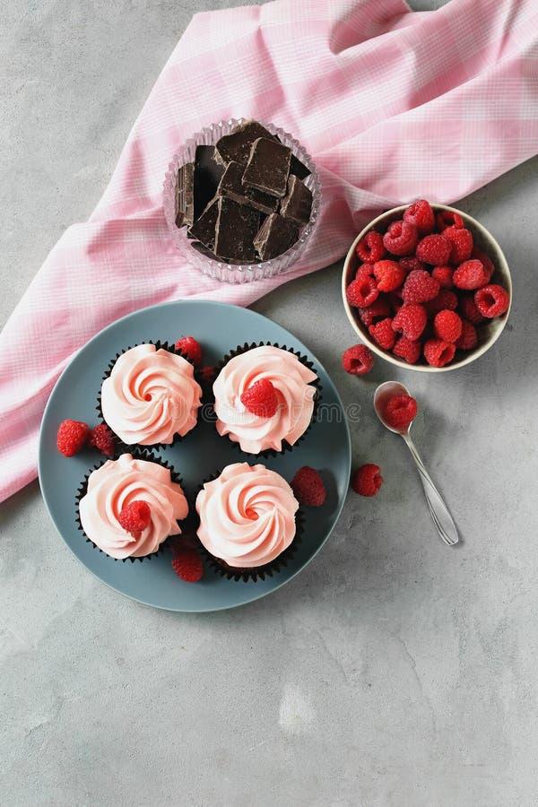 Plaat met smakelijke cupcakes, chocolade en framboos op grijze lijst stock fotografie