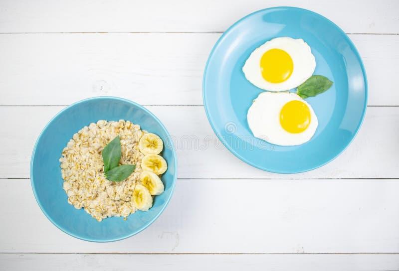 Plaat met smakelijke havermeel en banaanplakken en gebraden eieren op witte houten achtergrond Gezond conceptenbeeld van ontbijt, royalty-vrije stock foto