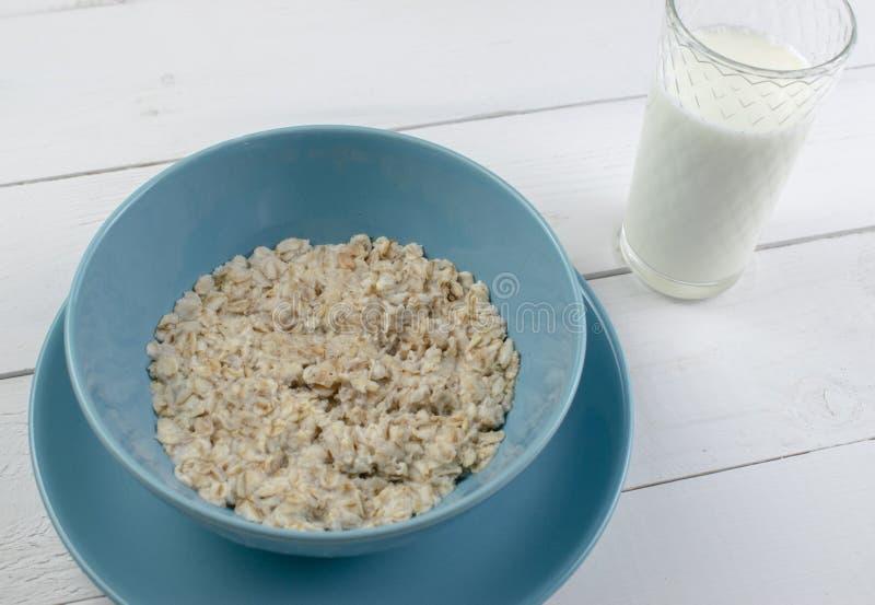 Plaat met smakelijke havermeel en banaanplakken op witte houten achtergrond Conceptenbeeld van ontbijt, het gezonde eten stock foto