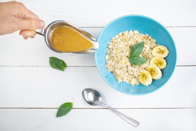 Plaat met smakelijke havermeel en banaanplakken op witte houten achtergrond Conceptenbeeld van ontbijt, het gezonde eten royalty-vrije stock afbeelding