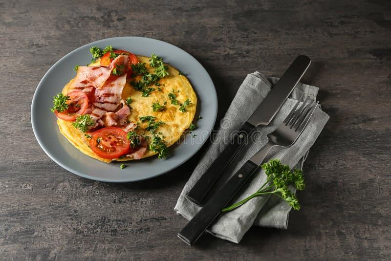 Plaat met smakelijke omelet en bacon op grijze lijst stock foto