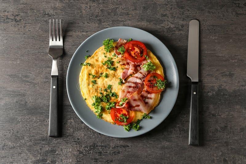 Plaat met smakelijke omelet en bacon op grijze lijst stock fotografie