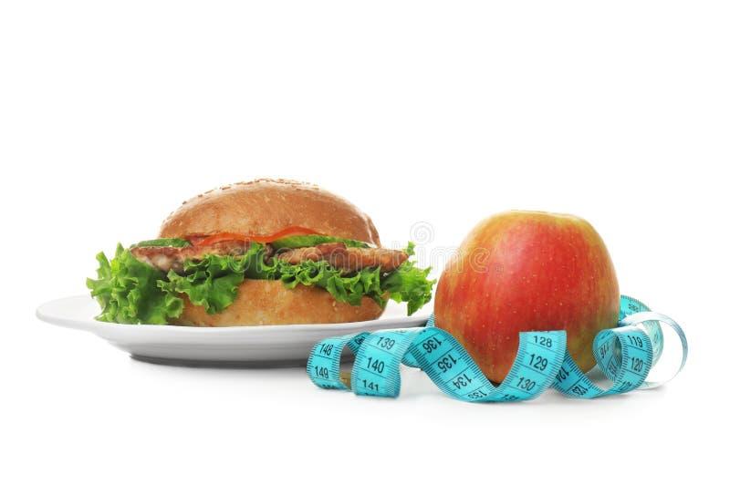 Plaat met smakelijke sandwich, verse appel en het meten van band op witte achtergrond Keus tussen dieet royalty-vrije stock fotografie