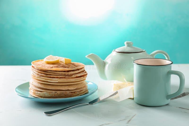 Plaat met stapel van heerlijke dunne pannekoeken, boter en thee op lichte lijst royalty-vrije stock foto