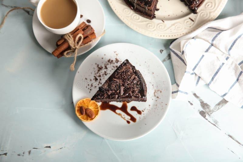 Plaat met stuk van heerlijke chocoladecake en kop van koffie op lichte lijst royalty-vrije stock afbeeldingen