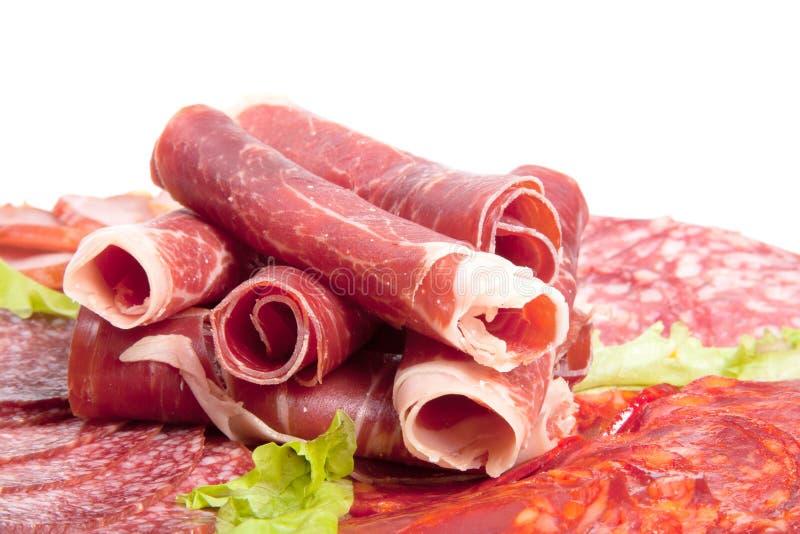 Plaat met verschillende vleesdelicatessen die op witte backgroun worden geïsoleerd stock foto