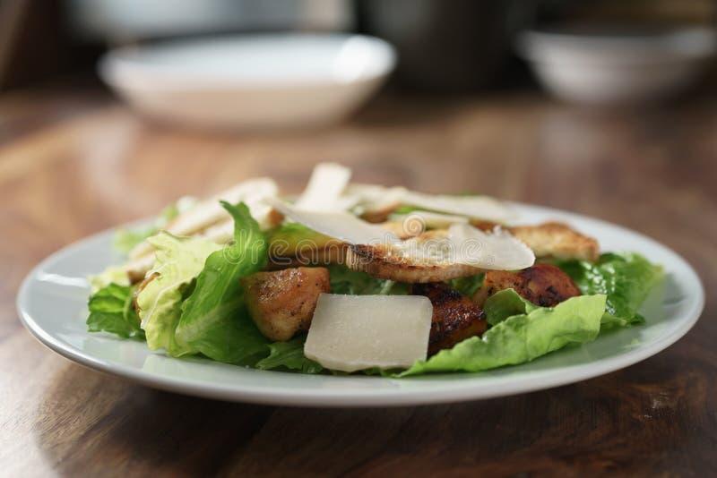 Plaat met verse caesar salade met kip op oude houten lijst stock afbeeldingen