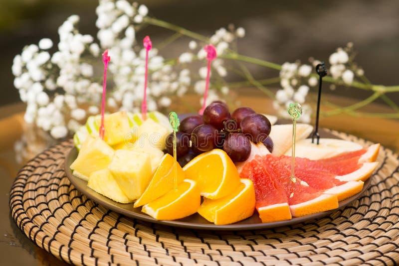 Plaat met verse gesneden vruchten Banaan, druiven grapefruit, sinaasappel stock foto's