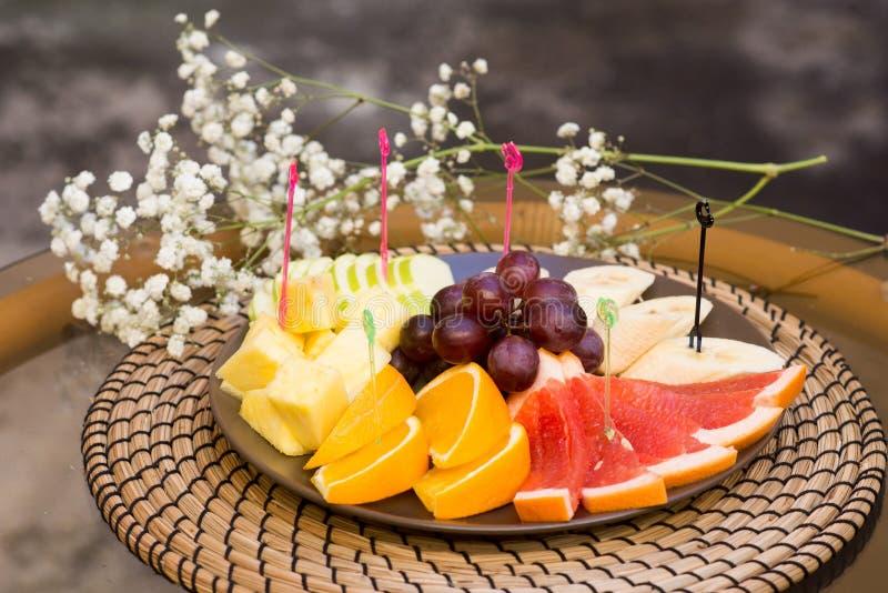Plaat met verse gesneden vruchten Banaan, druiven grapefruit, sinaasappel royalty-vrije stock afbeelding