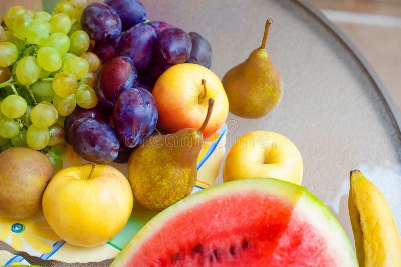 Plaat met vruchten - appelen, peren, pruimen, druiven Gezond voedselconcept stock foto