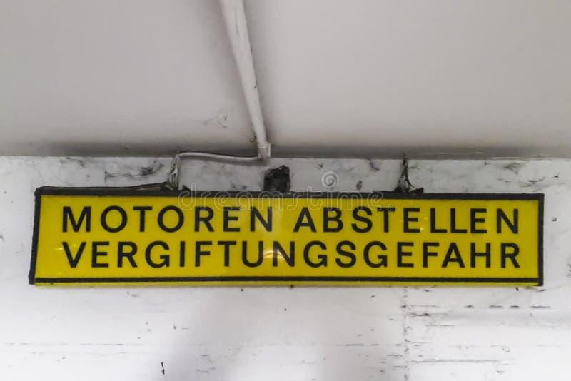 Plaat: Motoren abstellen Vergiftungsgefahr op een grijze achtergrond stock foto's